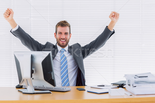 Cheerful businessman clenching fist at office desk Stock photo © wavebreak_media