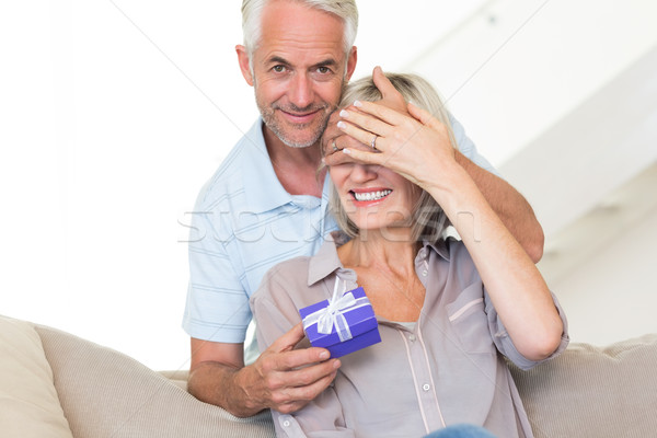 Smiling mature man surprising woman with a gift Stock photo © wavebreak_media