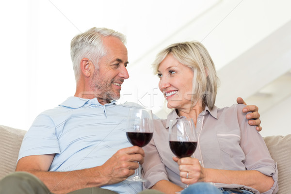 Smiling mature couple with wine glasses sitting on sofa Stock photo © wavebreak_media