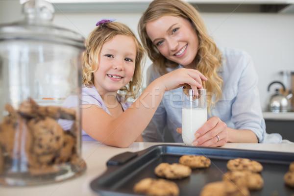 Mother with girl dipping cookie in milk Stock photo © wavebreak_media