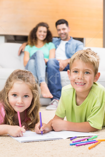Happy siblings colouring on the rug with parents watching from s Stock photo © wavebreak_media