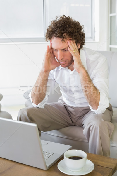 Worried man with head in hands looking at laptop at home Stock photo © wavebreak_media