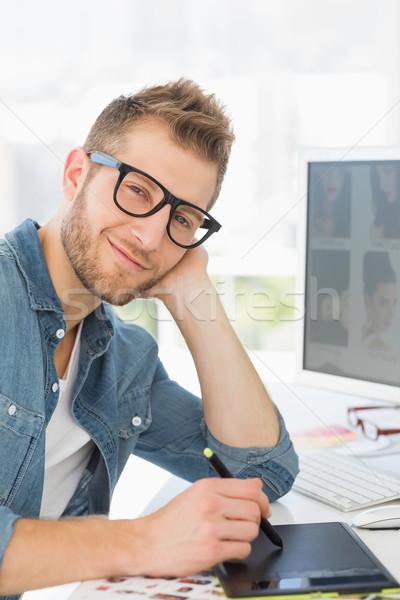 Bonito estilista trabalhando gráficos comprimido sorridente Foto stock © wavebreak_media