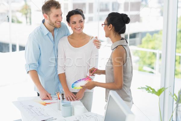 Interior designer showing colour wheel to happy young clients Stock photo © wavebreak_media