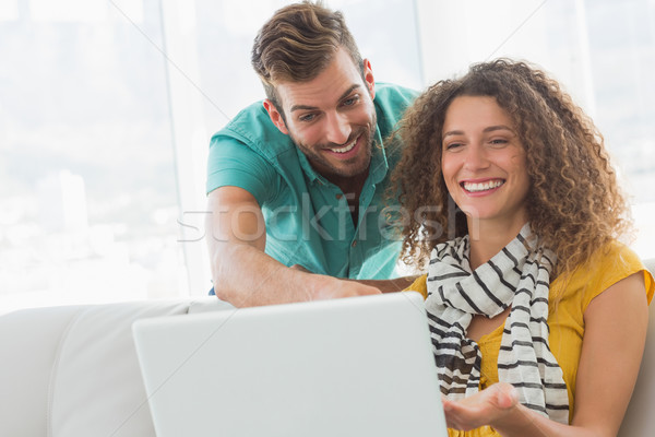 Smiling woman on the couch showing her co worker her laptop Stock photo © wavebreak_media