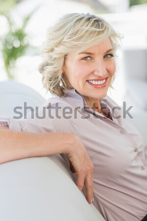 Stock photo: Sexy young blonde buttoning up white shirt smiling at camera