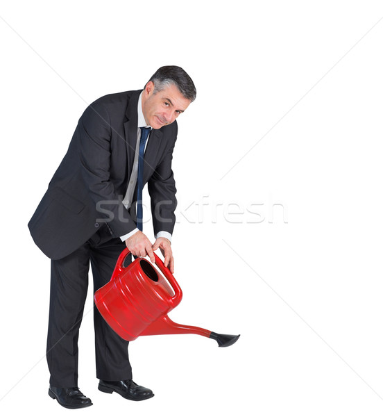 Mature businessman watering with red can Stock photo © wavebreak_media