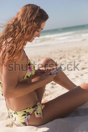 Pretty blonde woman sitting on the beach applying suncream Stock photo © wavebreak_media