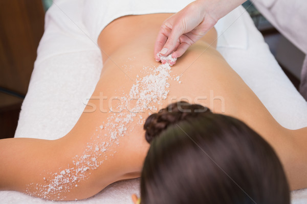 Stock photo: Beauty therapist pouring salt scrub on womans back