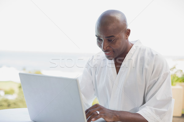 Knappe man badjas met behulp van laptop ontbijt buiten Stockfoto © wavebreak_media