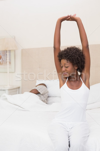 Pretty woman stretching at end of bed Stock photo © wavebreak_media
