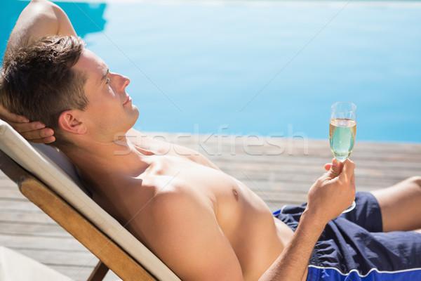 Fiatalember tart pezsgő furulya úszómedence oldalnézet Stock fotó © wavebreak_media