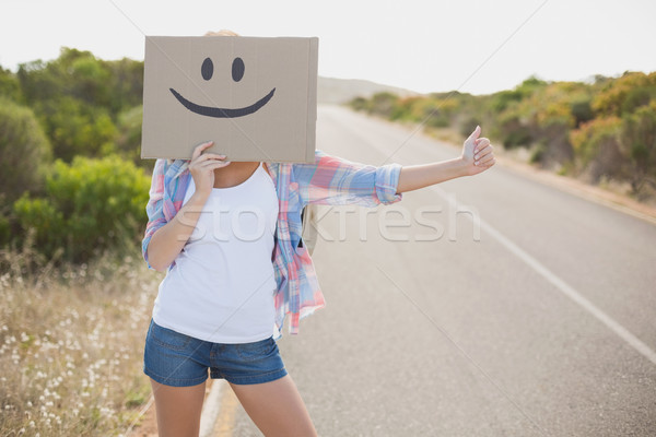 Woman with smiley face hitchhiking on countryside road Stock photo © wavebreak_media