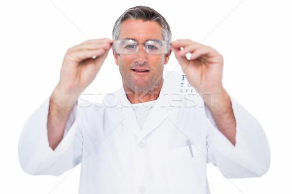 Optician in coat holding glasses  Stock photo © wavebreak_media