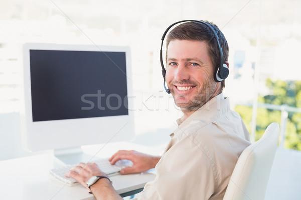 Businessman in headset smiling at camera Stock photo © wavebreak_media