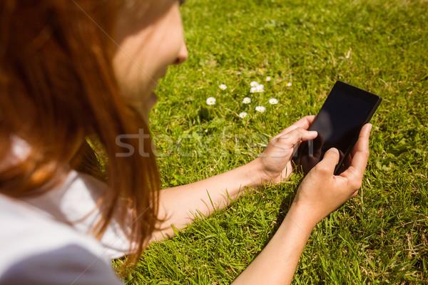 Pretty redhead text messaging on her phone Stock photo © wavebreak_media