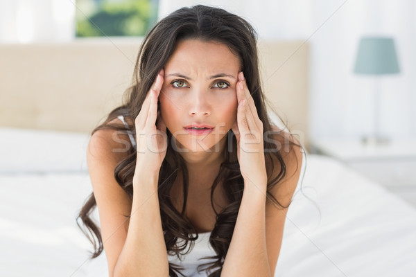 Worried brunette sitting on bed Stock photo © wavebreak_media