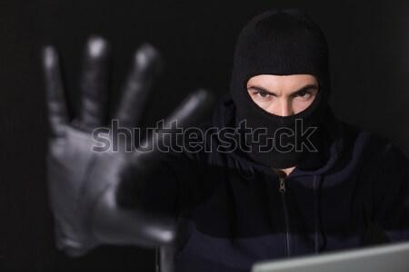 Hacker in balaclava gesturing and using laptop Stock photo © wavebreak_media