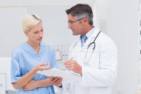 Doctor and nurse discussing over notes in clinic Stock photo © wavebreak_media