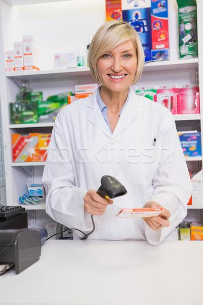 Smiling pharmacist scanning box of medicine Stock photo © wavebreak_media