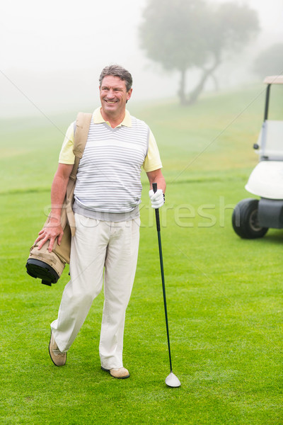 Happy golfer with golf buggy behind  Stock photo © wavebreak_media