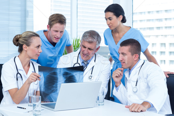 Team of doctors working on laptop and analyzing xray Stock photo © wavebreak_media