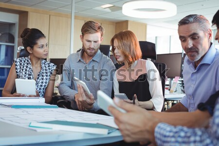 Casual business people shaking hands at desk and smiling Stock photo © wavebreak_media