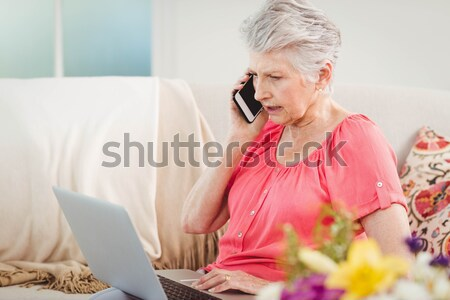 Beautiful blonde using laptop on couch with pet dog Stock photo © wavebreak_media