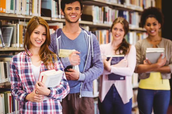 Happy students holding books in row Stock photo © wavebreak_media
