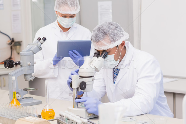 Scientists using tablet pc and microscope  Stock photo © wavebreak_media