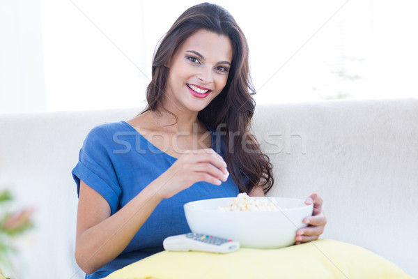 Smiling beautiful brunette relaxing on the couch with bowl of po Stock photo © wavebreak_media