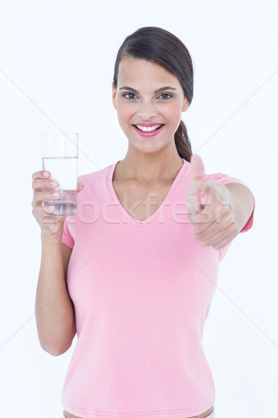Beautiful woman drinking glass of water with thumb up Stock photo © wavebreak_media