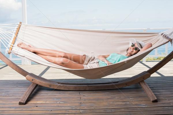 довольно брюнетка расслабляющая гамак патио морем Сток-фото © wavebreak_media