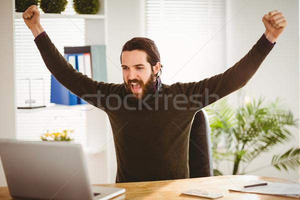Hipster businessman cheering at his desk Stock photo © wavebreak_media