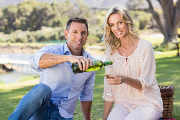 Portrait of smiling couple sitting and pouring wine in glass  Stock photo © wavebreak_media