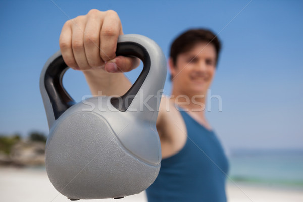 Stock photo: Low angle view of man holding kettlebell at beach