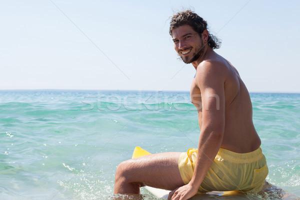 Sorridente surfista sessão prancha de surfe retrato praia Foto stock © wavebreak_media