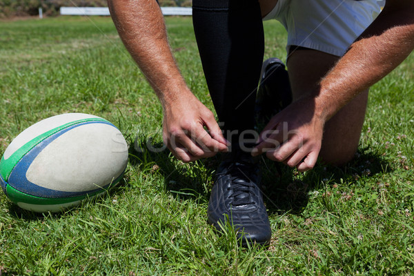 Rugby player tying shoes on field Stock photo © wavebreak_media
