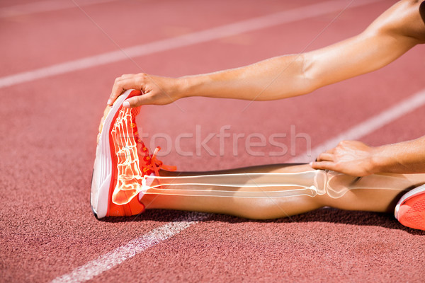 Low section of sportswoman stretching on track during Stock photo © wavebreak_media