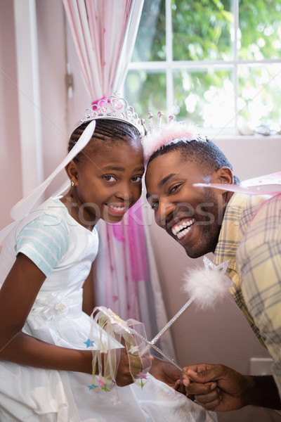 Cheerful father and daughter holding wands while wearing costumes Stock photo © wavebreak_media