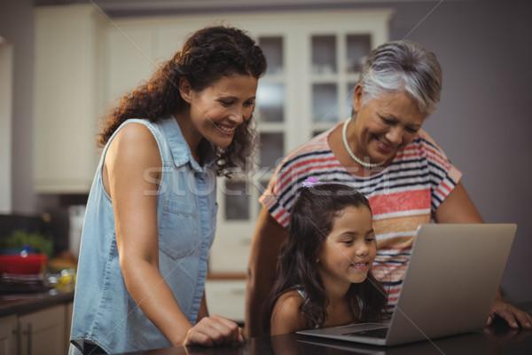 Happy family using laptop in kitchen Stock photo © wavebreak_media