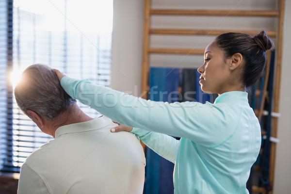 Female therapist examining neck of senior male patient Stock photo © wavebreak_media