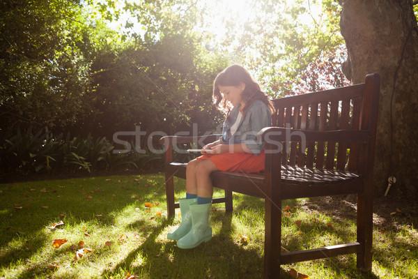 Souriant fille bois banc séance Photo stock © wavebreak_media