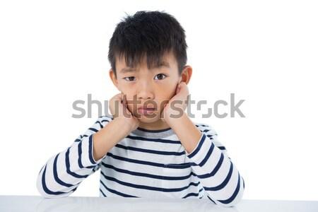 Sad boy sitting against white background Stock photo © wavebreak_media