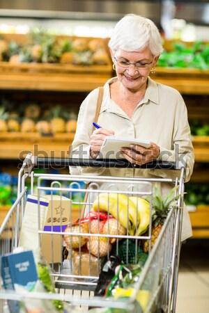 Smiling senior woman pushing trolley Stock photo © wavebreak_media