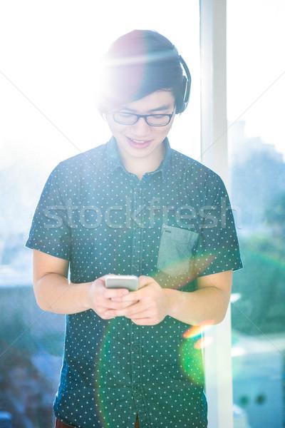 Smiling hipster businessman listening music Stock photo © wavebreak_media