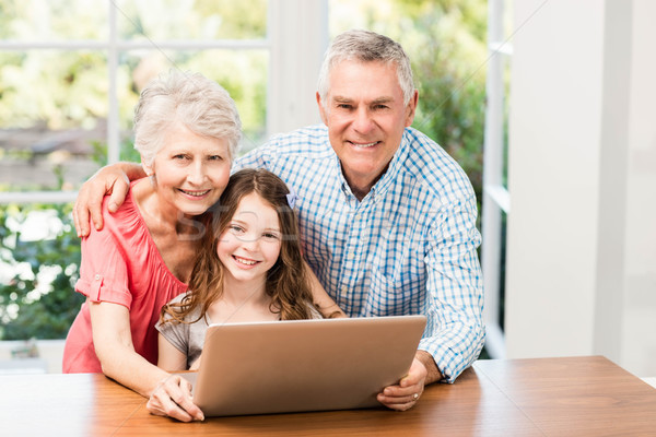 Portrait of smiling grandparents and granddaughter using laptop Stock photo © wavebreak_media