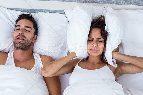 Woman blocking ears while man snoring on bed Stock photo © wavebreak_media