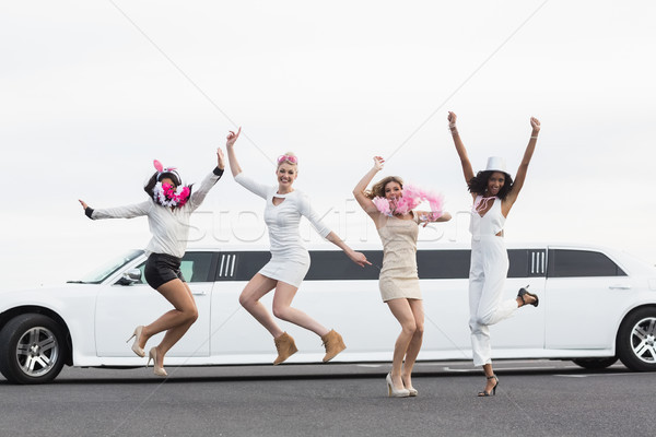 Happy friends jumping in front of a limousine Stock photo © wavebreak_media