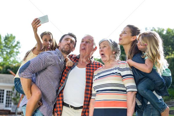 Cheerful girl taking selfie with multi-generation family Stock photo © wavebreak_media